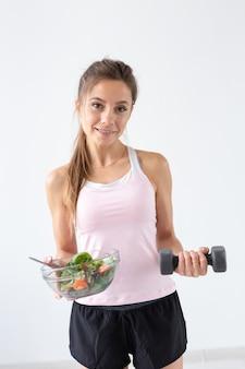 Gesunder lebensstil, menschenkonzept - ein salatteller in einer hand und eine hantel in der anderen hand. lächeln und fitnessanzug.