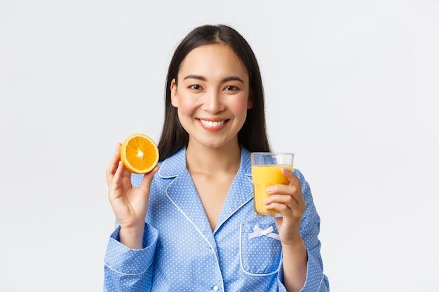 Gesunder lebensstil, morgenroutine und menschenkonzept. nahaufnahme des asiatischen mädchens im blauen pyjama mit perfekter sauberer haut, zeigt ihre tägliche gewohnheit, frisch gemachten orangensaft zu trinken, lächelnd erfreut.