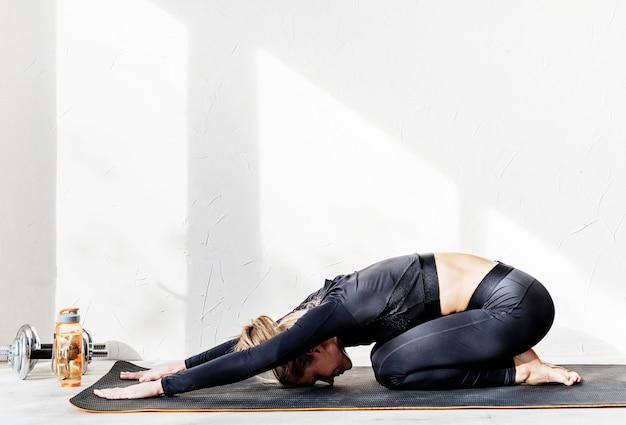 Gesunder lebensstil. sport und fitness. junge athletische frau, die zu hause arbeitet oder yoga streckt