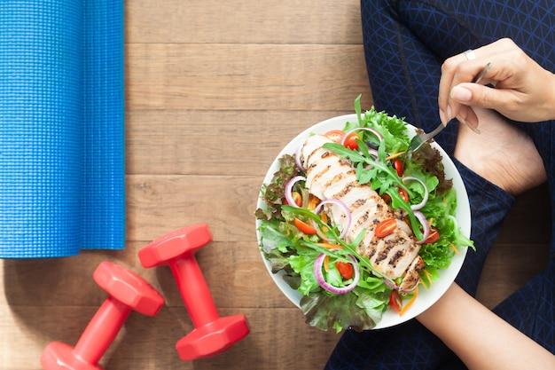 Gesunder lebensstil. sportliche frau, die salat isst. flach legen