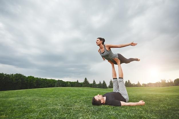 Gesunder lebensstil starker mann, der auf gras liegt und frau auf seinen füßen balanciert junges paar
