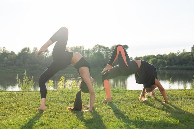 Gesunder lebensstil und harmoniekonzept - junge mädchen, die yoga im freien machen
