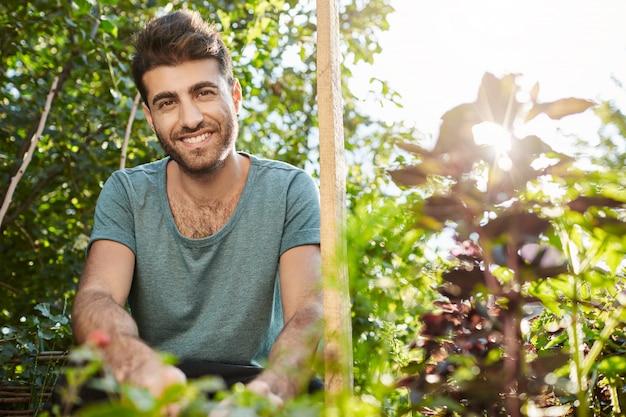 Gesunder lebensstil. vegetarisches essen. schließen sie herauf porträt des jungen fröhlichen bärtigen kaukasischen mannes lächelnd, im garten arbeitend.