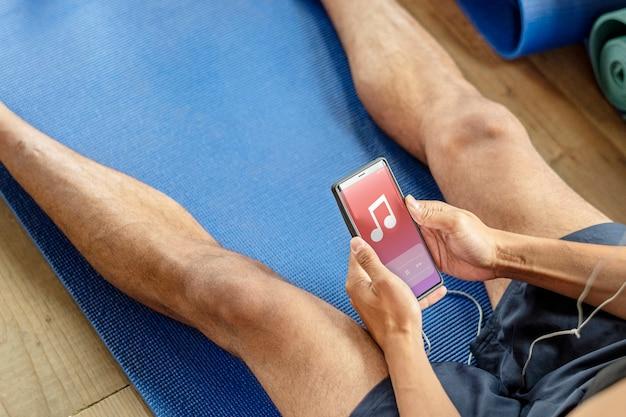 Gesunder mann, der in einem fitnessstudio musik hört