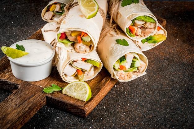 Gesunder mittagssnack. stapel mexikanische straßenlebensmittel-fajitatortillaverpackungen mit gegrillter büffelhühnerleiste und frischgemüse