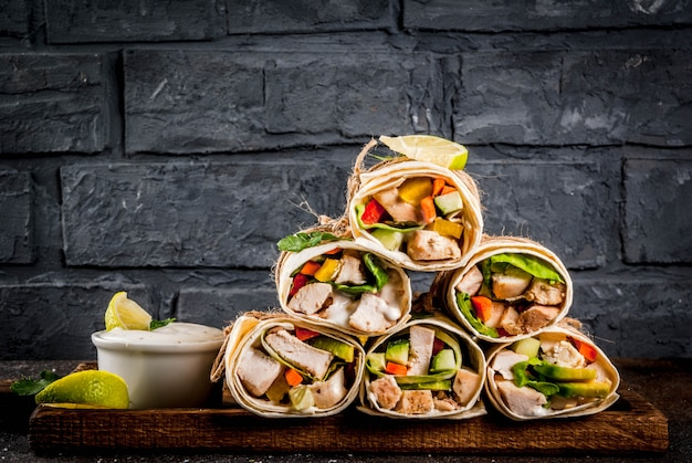 Gesunder mittagssnack. stapel mexikanische straßenlebensmittel-fajitatortillaverpackungen mit gegrillter büffelhühnerleiste und -gemüse