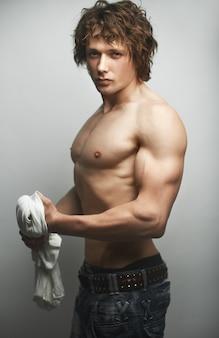 Gesunder muskulöser junger mann mit towell