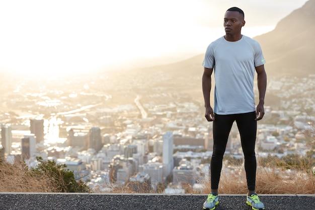 Gesunder nachdenklicher athletischer mann mit fitem körper, steht auf hügel gegen stadtblick, trägt freizeitkleidung, freien platz auf der linken seite für ihren werbeinhalt. menschen, motivation und energiekonzept
