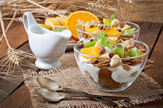 Gesunder nachtisch mit müsli und frucht in einer glasschüssel auf dem tisch