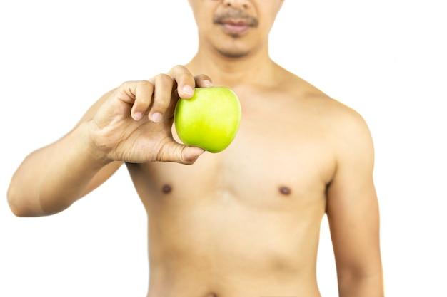 Gesunder nackter mann, der einen frischen grünen apfel lokalisiert im beschneidungspfad hält.
