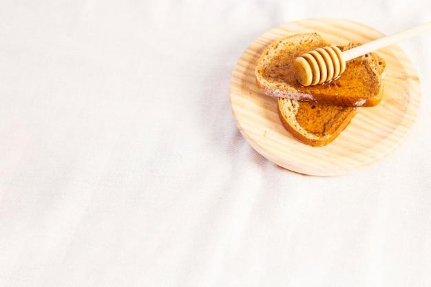 Gesunder natürlicher honig und brot in der platte über weißem stoff