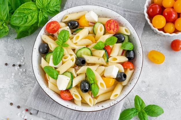 Gesunder nudelsalat mit tomaten, gurken, roten zwiebeln, oliven und käse in einer schüssel