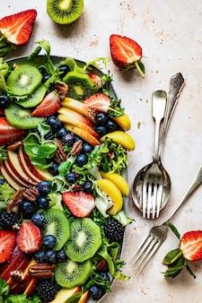 Gesunder obstsalat mit gemüse und pekannüssen