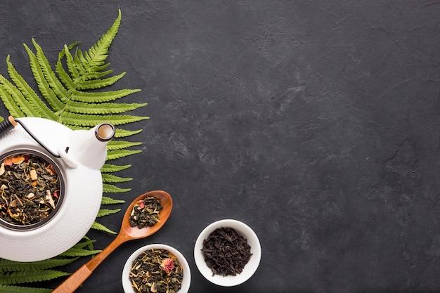 Gesunder organischer tee mit trockenem kraut und farn verlässt auf schwarzer oberfläche