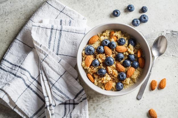Gesunder quinoa-brei mit blaubeeren und mandeln mit sirup in grauer schüssel, kopienraum. veganes lebensmittelkonzept.