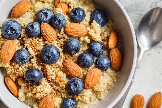 Gesunder quinoabrei mit blaubeeren und mandeln mit sirup in der grauen schüssel, draufsicht. veganes food-konzept.