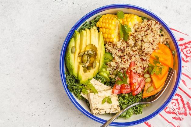 Gesunder regenbogensalat des strengen vegetariers, buddha-schüssel mit quinoa, tofu, avocado und kohl, kopienraum. gesundes sauberes essenkonzept.