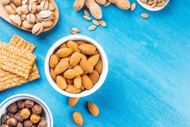 Gesunder riegel mit erdnüssen; haselnüsse; pistazie und mandeln auf blauem beschaffenheitshintergrund