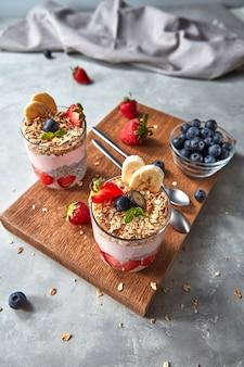 Gesunder rosa smoothie in gläsern mit natürlichen früchten erdbeere, banane, blaubeere