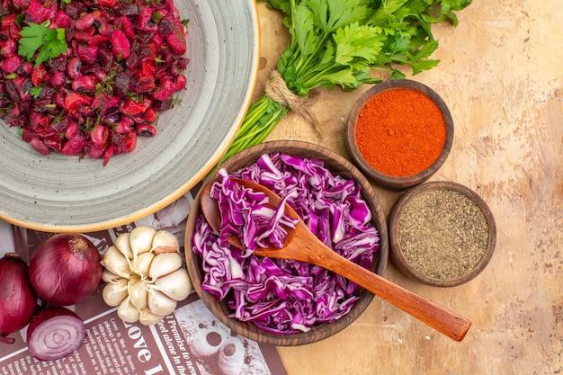 Gesunder rote-bete-salat von oben auf einer grauen keramikplatte mit roten zwiebeln, knoblauch und petersilie und einer schüssel mit schwarzem pfeffer, kurkuma, gemahlenem pfeffer, rotkohl auf einem holztisch