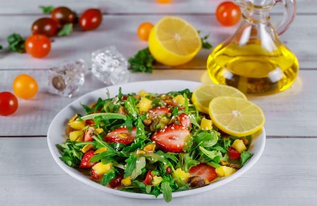 Gesunder rucola-salat mit erdbeeren, ananas und pistazien, sesam, öl und zitrone