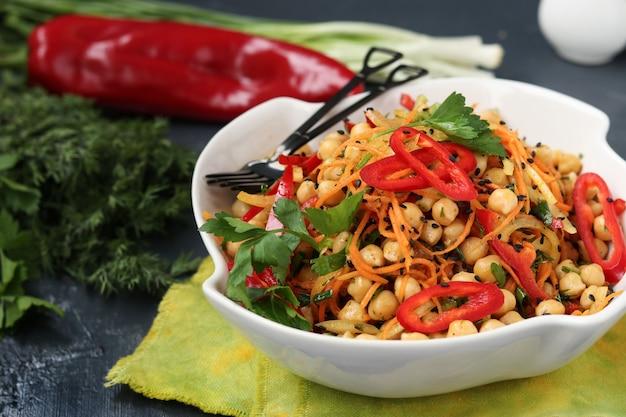 Gesunder salat aus kichererbsen, koreanischen karotten, paprika und zwiebeln, dekoriert mit schwarzem sesam und petersilie