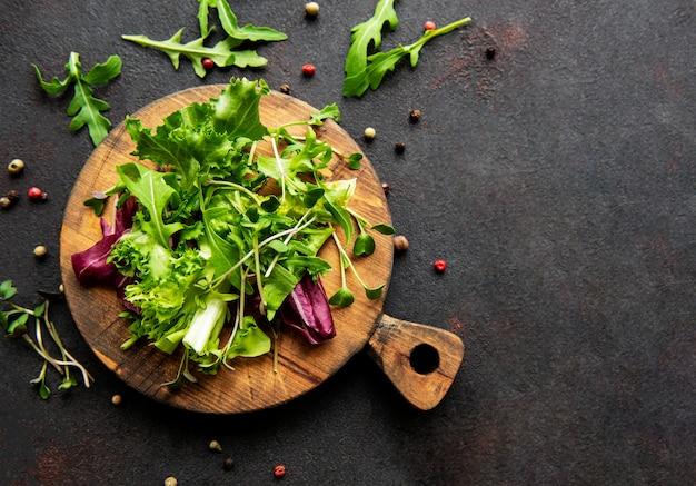 Gesunder salat, blätter mischen salat auf einem holzbrett auf schwarz