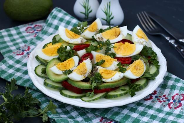 Gesunder salat der avocado, der gurken, der eier und des gemüsepaprikas gelegen in einer platte