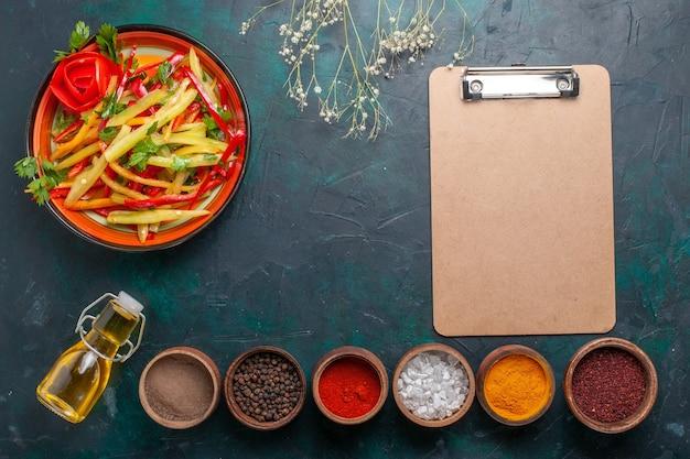 Gesunder salat der geschnittenen paprika der draufsicht mit olivenöl und gewürzen auf dunkelblauem hintergrund