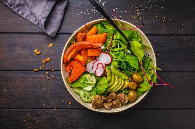 Gesunder salat des strengen vegetariers mit gebackenem gemüse, avocado und oliven in der weißen schüssel auf dunklem holz