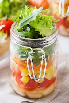 Gesunder salat im weckglas mit weißen bohnen, tomaten, zwiebel, mais und kopfsalat auf holztisch