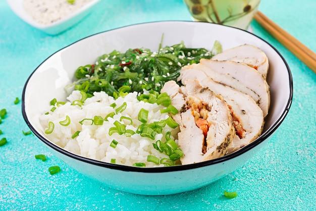 Gesunder salat in einer weißen schüssel, essstäbchen. hühnerbrötchen, reis, chuka und frühlingszwiebeln.