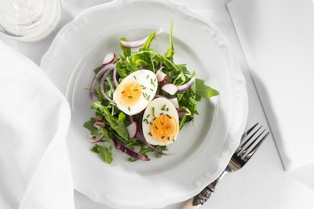 Gesunder salat mit ei auf einer weißen telleranordnung