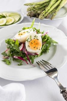 Gesunder salat mit ei auf einer weißen tellerzusammensetzung