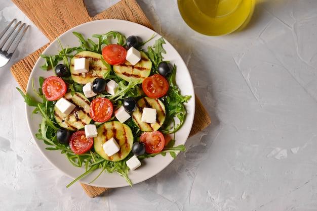 Gesunder salat mit feta-käse auf grauem tisch