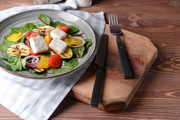 Gesunder salat mit feta-käse auf holztisch