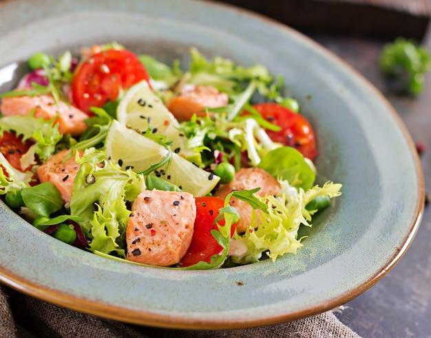 Gesunder salat mit fisch. gebackener lachs, tomaten, limette und salat. gesundes abendessen.