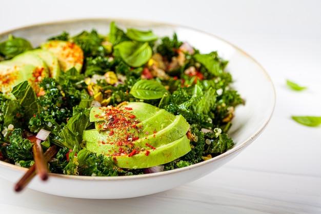Gesunder salat mit grünkohl, quinoa, nüssen und avocado in einer weißen schüssel. gesundes veganes lebensmittelkonzept.
