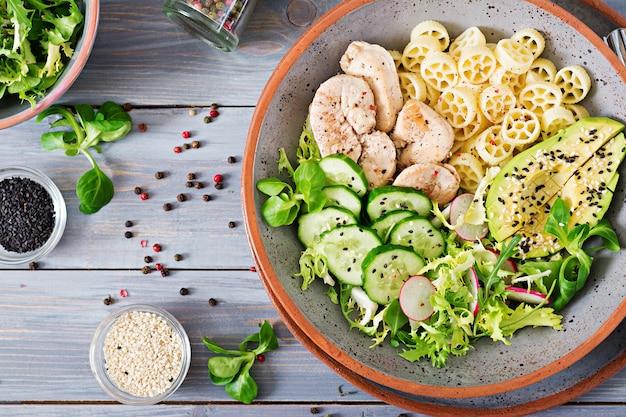 Gesunder salat mit huhn, avocado, gurke, kopfsalat, rettich und teigwaren auf dunkelheit
