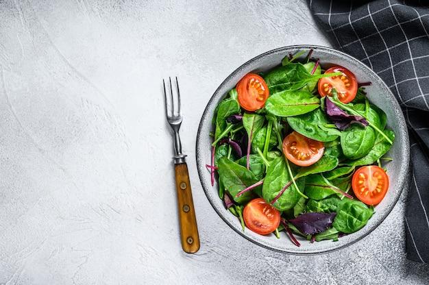 Gesunder salat mit mischung blätter mangold, mangold, spinat und rucola in einer salatschüssel. weißer hintergrund. draufsicht. speicherplatz kopieren.