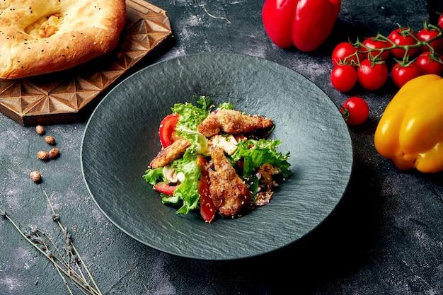 Gesunder salat mit pilzen, tomaten, salat und gebackenem huhn in einem schwarzen teller