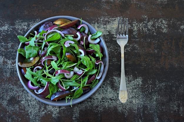 Gesunder salat mit rucola, pflaume und blauen zwiebeln in einer schüssel auf einem stilvollen schäbigen hintergrund