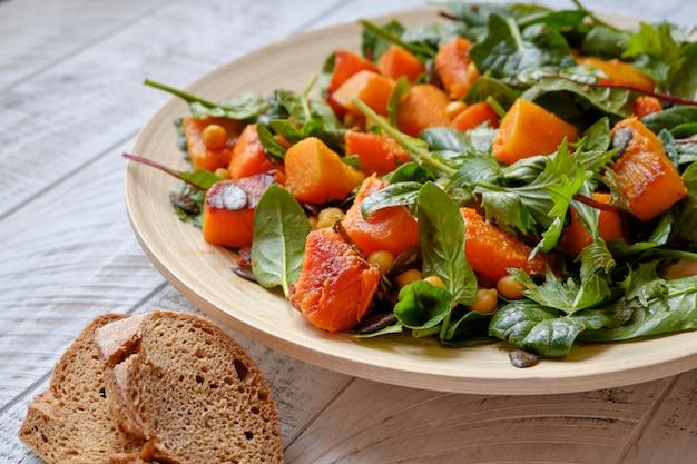 Gesunder salat mit spinat und sautiertem kürbis