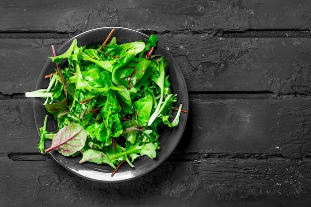 Gesunder salat. rucola-salat in einer schüssel. auf einem schwarzen rustikalen tisch.