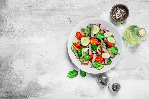 Gesunder salat. salat mit gekochtem rindfleisch, gemüse und wachteleiern.
