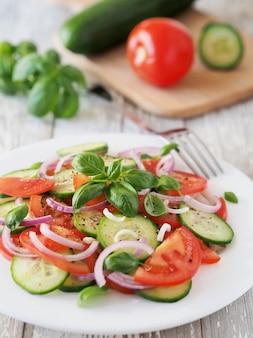 Gesunder salat von frischen tomaten und gurken mit basilikum auf einem weißen rustikalen tisch