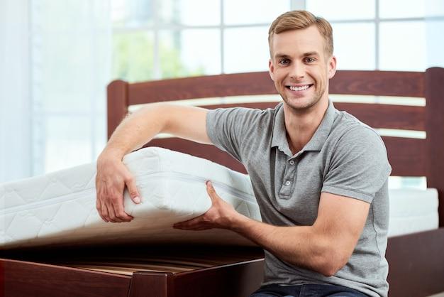 Gesunder schlaf junger und glücklicher gutaussehender mann, der große und bequeme ergonomische matratze an der kamera zeigt