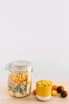 Gesunder selbst gemachter salat im weckglas und in den maissamen in der schale auf holztisch