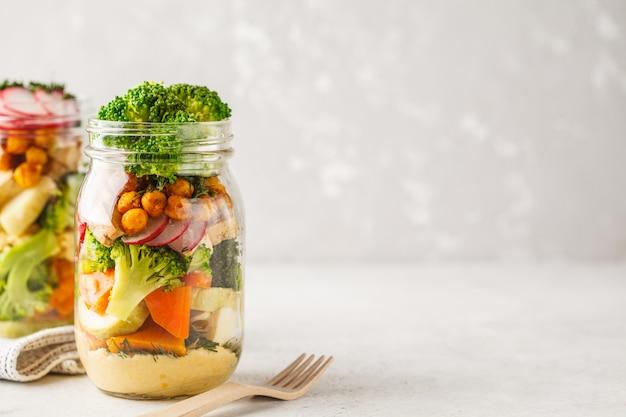 Gesunder selbst gemachter weckglas-salat mit gebackenem gemüse, hummus, tofu und kichererbsen, kopienraum.