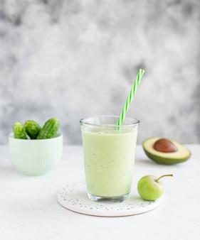 Gesunder smoothie mit avocadogurkenapfel in einem glas mit einem strohhalm